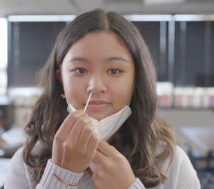 Image: girl swabbing her nose for a coronavirus test