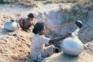 Young girls collecting water from holes dug in the ground, Udaipur, India.