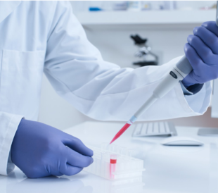A researcher with gloved hands uses a pipette