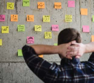 A founder looks at a wall of post-it notes