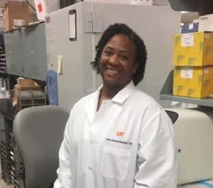 Dr. Athena Starlard-Davenport, a Black researcher in a lab coat, smiles in her lab, where she researches breast cancer