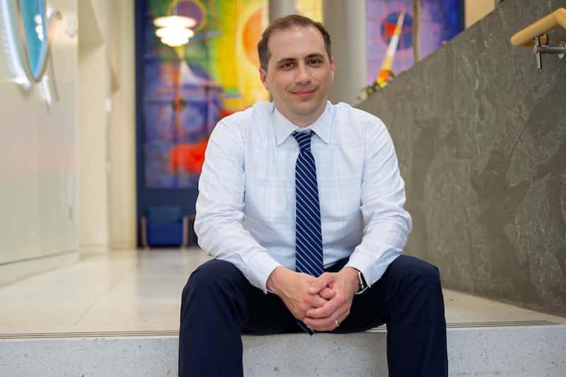 Dr. Philip Empey, who studies pharmacogenetics testing with clinical care, sits on the steps of a modern building interior.
