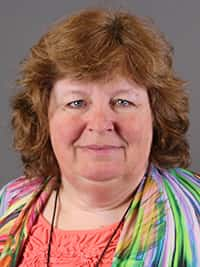 Marcia Slater, qPCR expert, has reddish hair and is wearing a red shirt and a rainbow cardigan