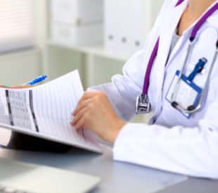 Doctor with confidential medical forms. Image: Micolas/Shutterstock.com