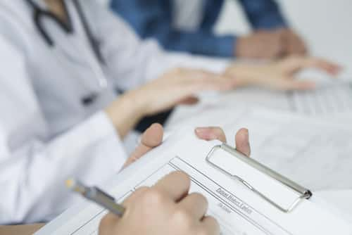 Medical interview being done with a clipboard. Image: Leonardo da/Shutterstock.com