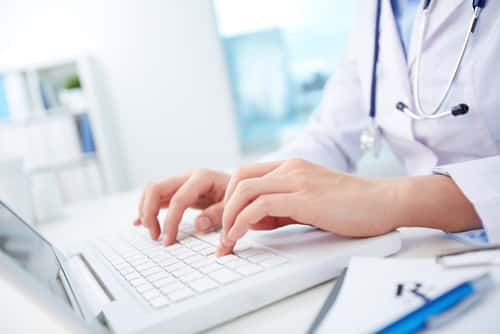 Close-up of hands of a nurse typing on laptop. Image: Kaspars Grinvalds/Shutterstock.com.