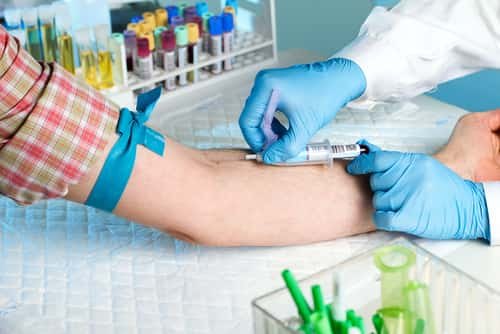 Laboratory with nurse taking a blood sample from patient, in background samples blood and urine tubes. Image: angellodeco/Shutterstock.com.