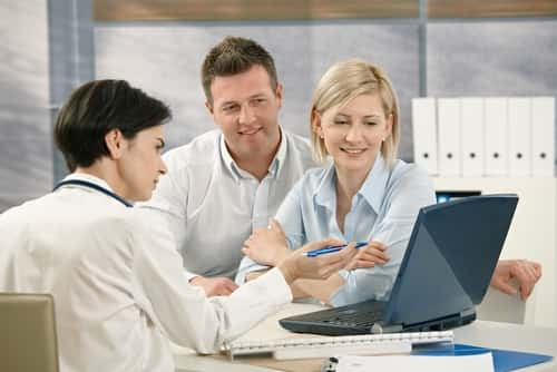 Medical doctor showing results to patients on computer in office. Image: StockLite/Shutterstock.com.