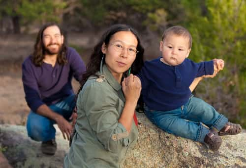 Young multicultural family in nature - shallow DOF - focus on mother & baby. Image: Mona Makela/Shutterstock.com.