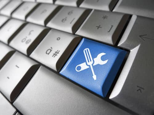 Assistance and computer service concept with toolkit icons and symbol on a blue laptop computer key for website and online business. Image: niroworld/Shutterstock.com.