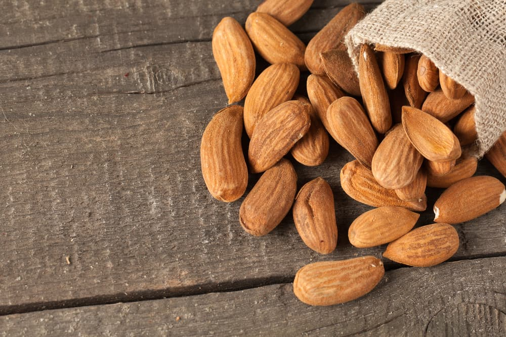 Raw almonds spilling out of a burlap bag onto a wooden background