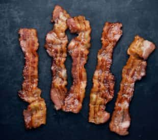 Cooked bacon strips on a black background