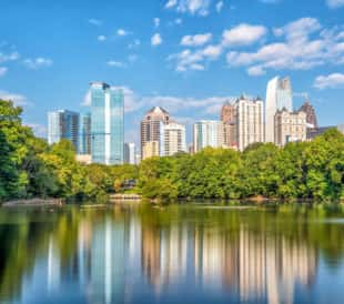 A view of Atlanta's tall buildings behind a lake and trees
