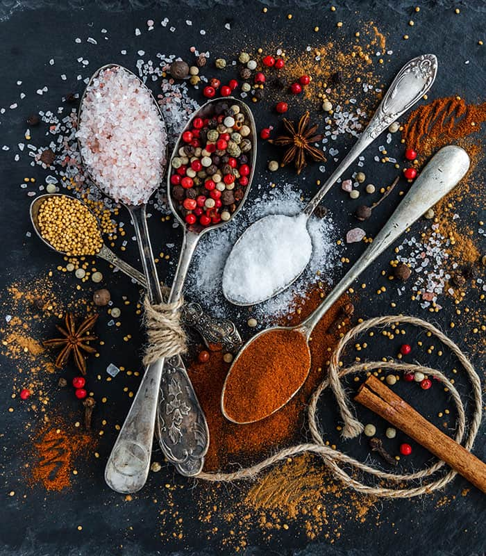 Commonly fraudulent herbs and spices sit in spoons on a black table