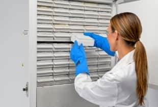 Scientist in front of ultra-low freezer