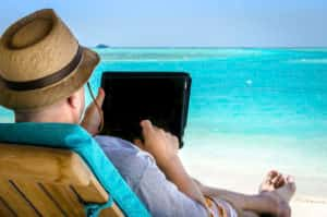 Mature man holding his digital tablet at his vacation on the beach