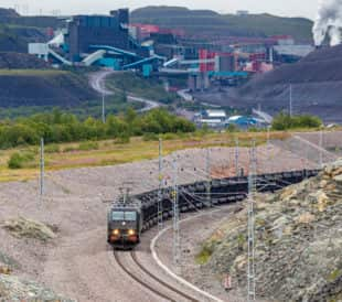 electric iron ore train passing mine operations