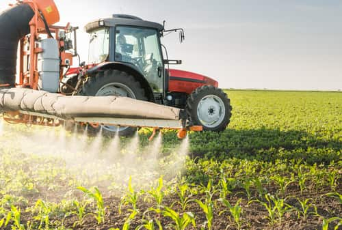Tractor spraying pesticides on soy bean. Image: Fotokostic/Shutterstock.com.