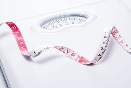 Close-up of a tape measure and bathroom scale. Image: kai keisuke/Shutterstock.com.