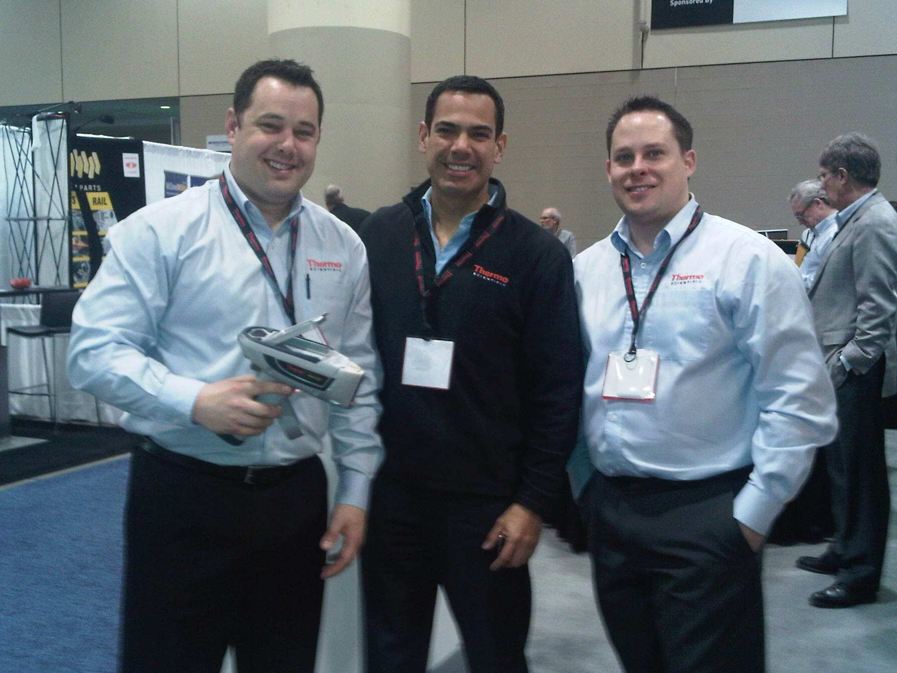 Happy booth staff posing with handheld XRF analyzer at PDAC