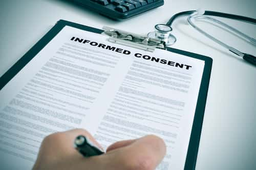 Person signing an informed consent form.