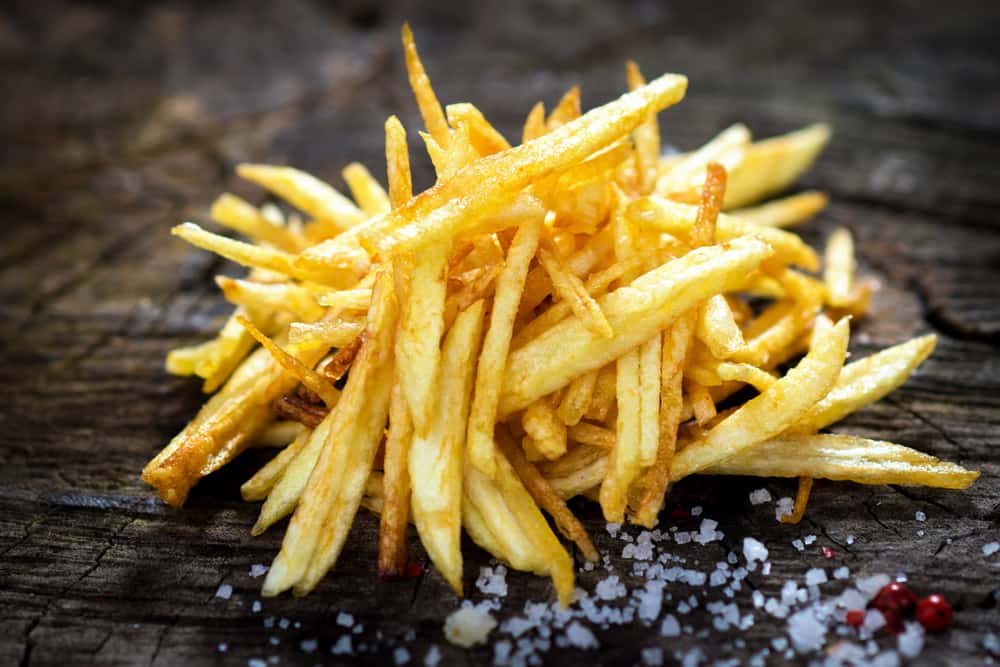 French fries with sea salt on a dark wooden background