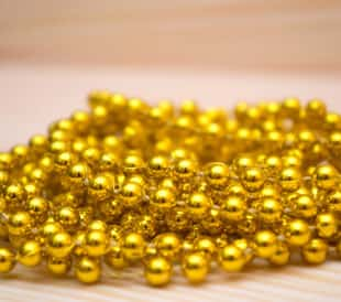 Pile of gold beads on a wooden table