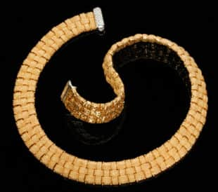 Basketweave gold necklace with diamonds on a black background