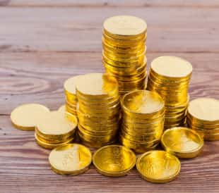 Stacked gold coins on a wooden background