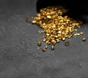 Pouch with scattered gold nugget grains on a cement background