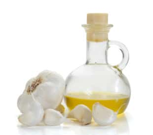 Garlic oil, isolated on a white background with fresh cloves of garlic