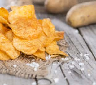 Heap of paprika potato chips on a rustic background