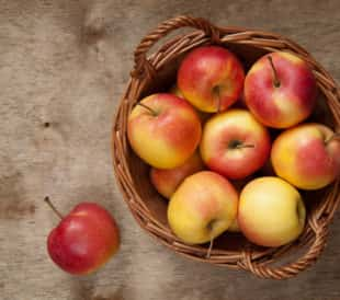 Red and yellow apples in a basket on a wooden table