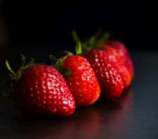 Strawberries lined up on a black background
