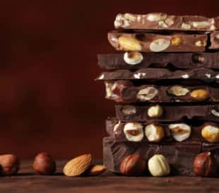 Light and dark chocolate bars with nuts layered on a brown background