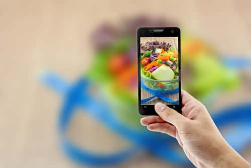 Smartphone taking a picture of a salad. Image Narith Thongphasuk/Shutterstock.com