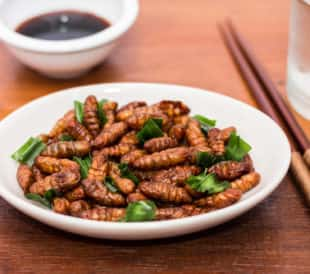 A bowl of fried bamboo worms with pandan, next to a bowl of soy sauce and chopsticks. Image: Charoenkrung.Studio99/Shutterstock.com