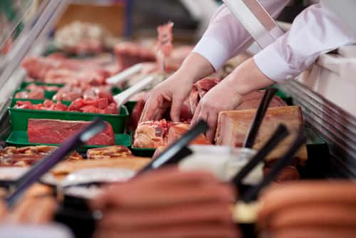 Two hands arrange meat in a display case. Image: stockfour/Shutterstock.com