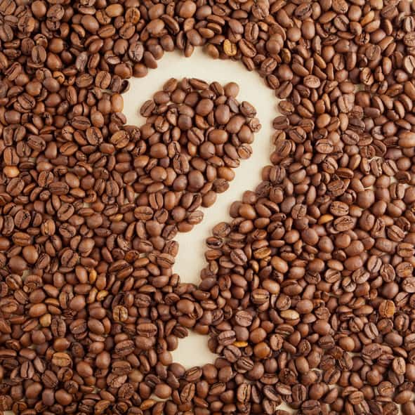 A pile of coffee beans shaped into a question mark.