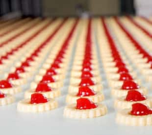 A tray of white cookies with red jelly in the middle.