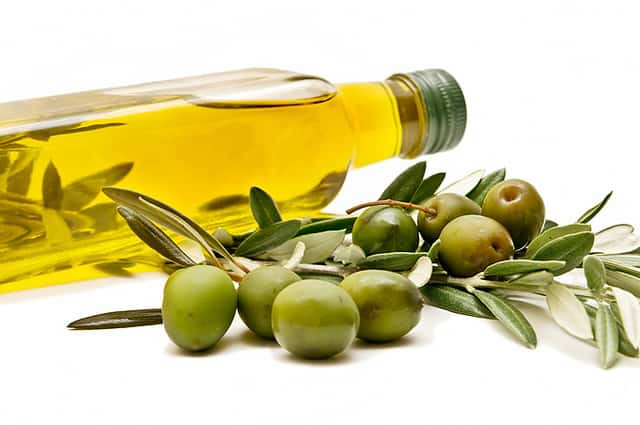 A bottle of olive oil lies on its side behind a branch of green olives