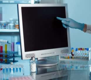 Scientist working with computer in a lab. Image: angellodeco/Shutterstock.com