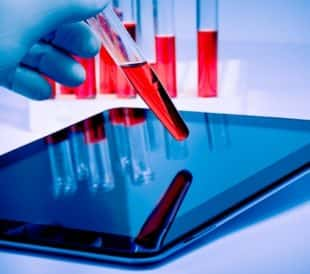 Researcher with test tube and tablet. Image: donfiore/Shutterstock.com