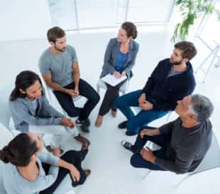 A group of patients sitting in a circle and talking. Image: wavebreakmedia/Shutterstock.com