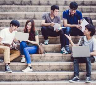 Group of teenagers sitting on stairs and talking. Image: Nonwarit/Shutterstock.com