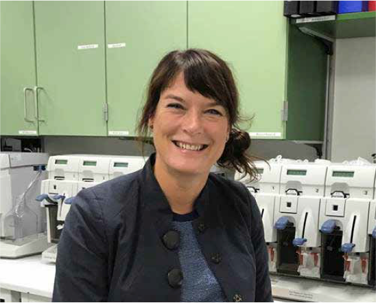 A female scientist smiles at the camera while sitting in her lab