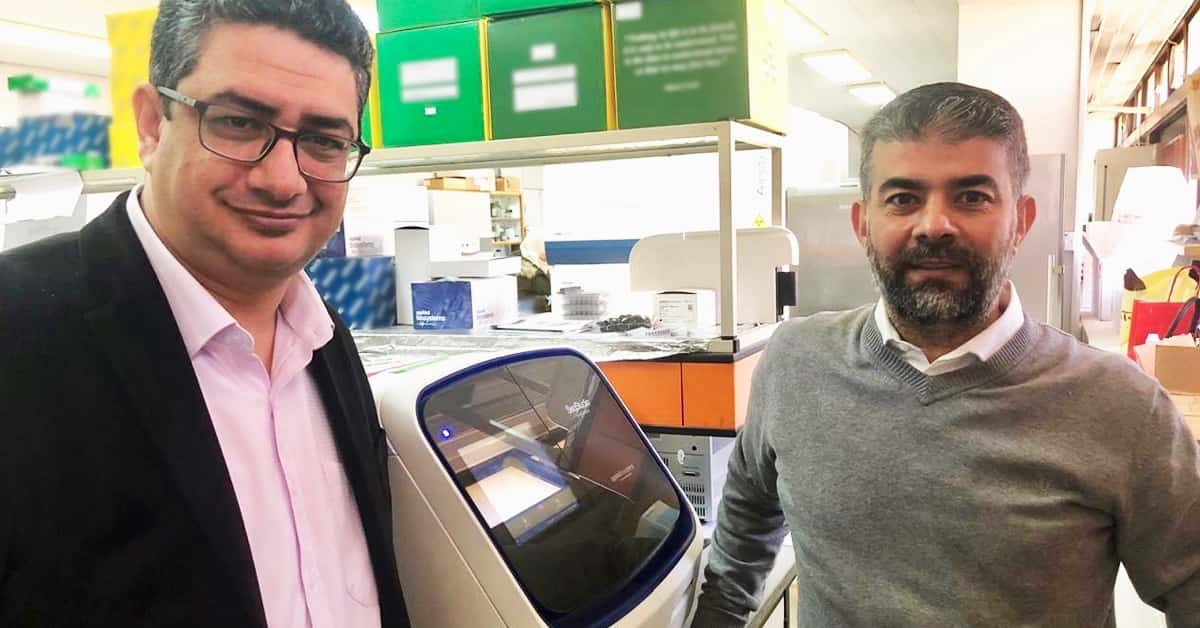 Dr. Mustafa Ababneh and Dr. Mohammad Alzghoul stand in their lab with Sanger sequencing equipment
