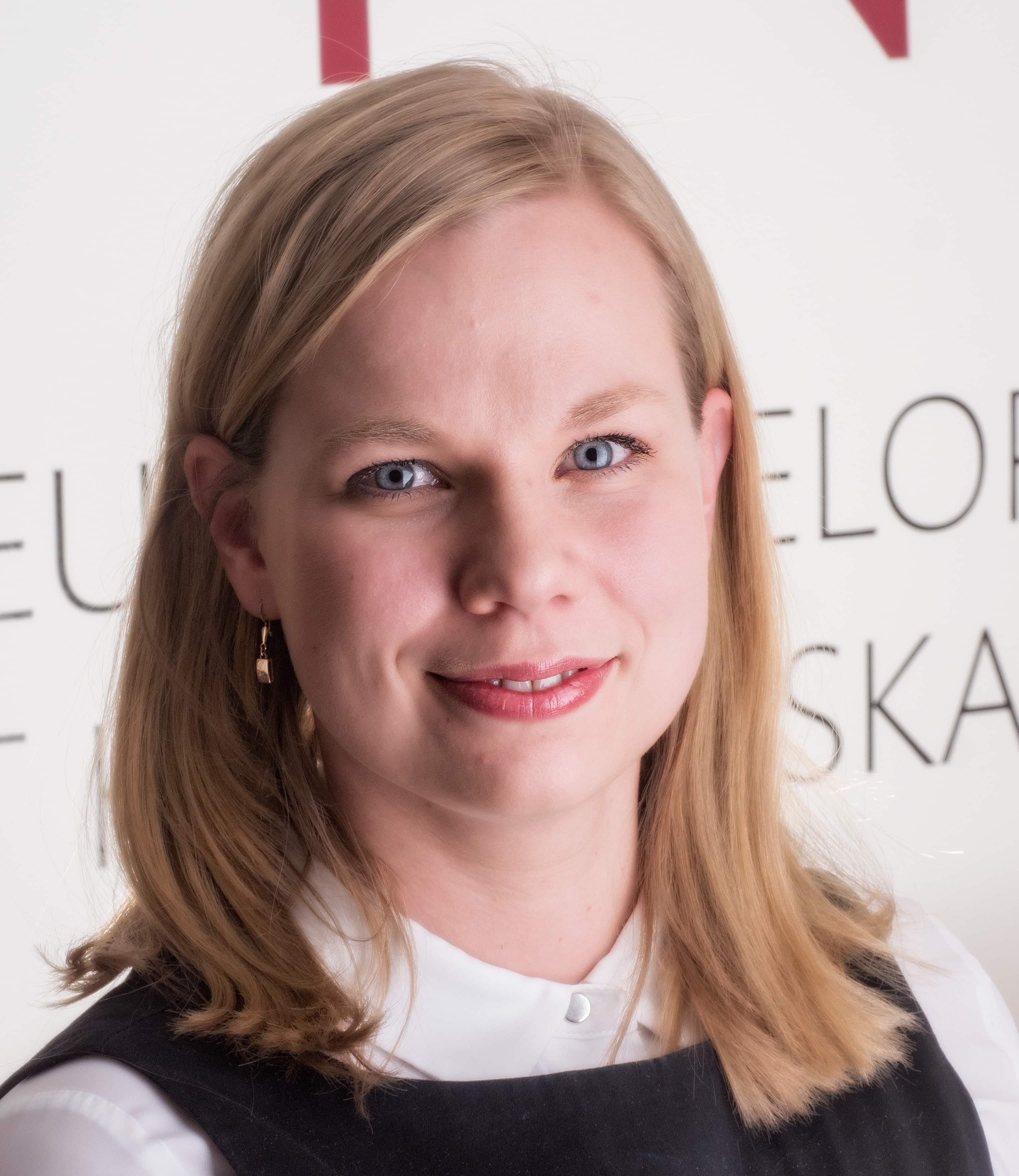 Dr. Kristiina Tammimies, a blonde researcher, smiles at the camera