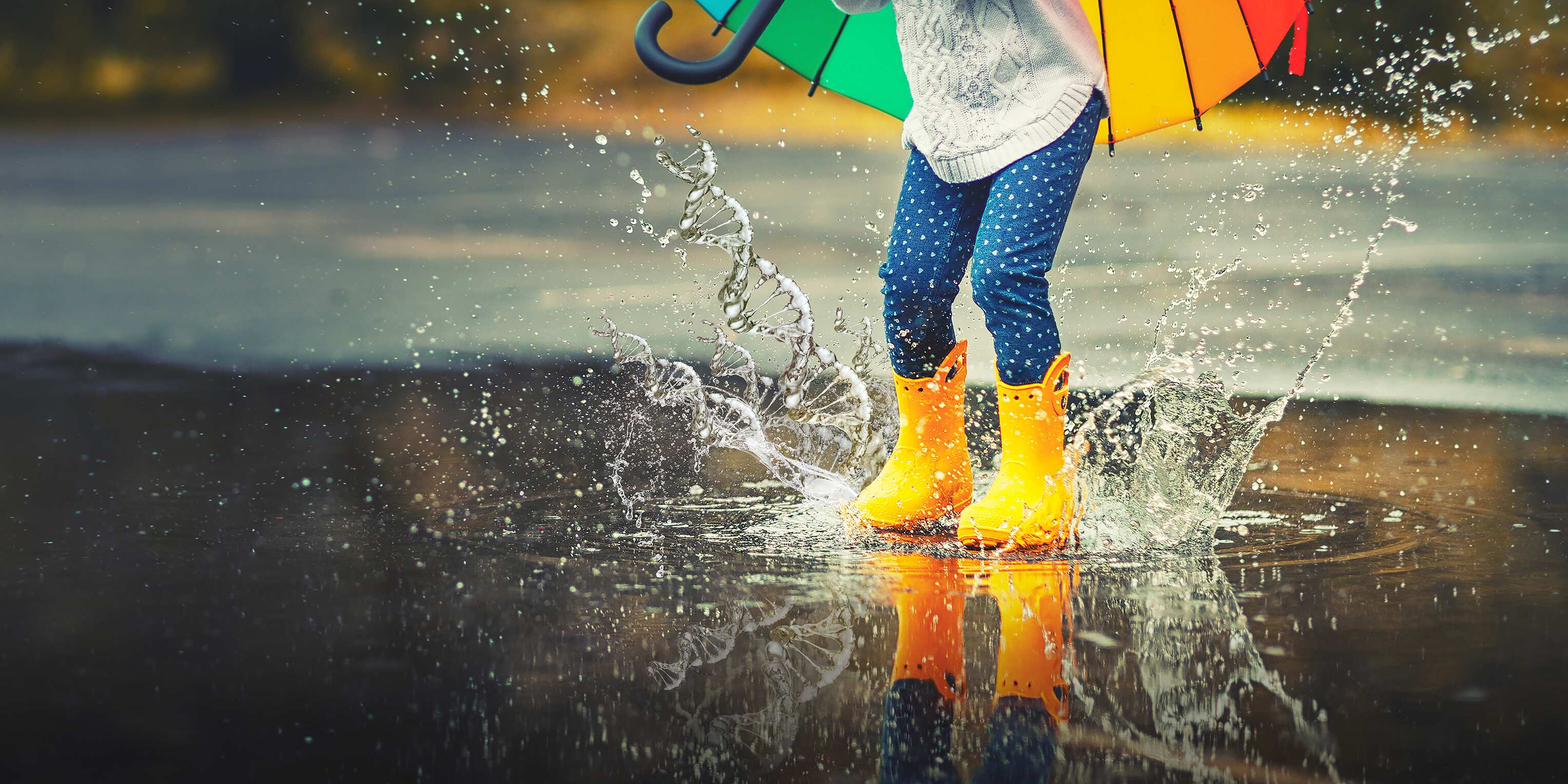 A child in yellow rain boots jumps into a puddle