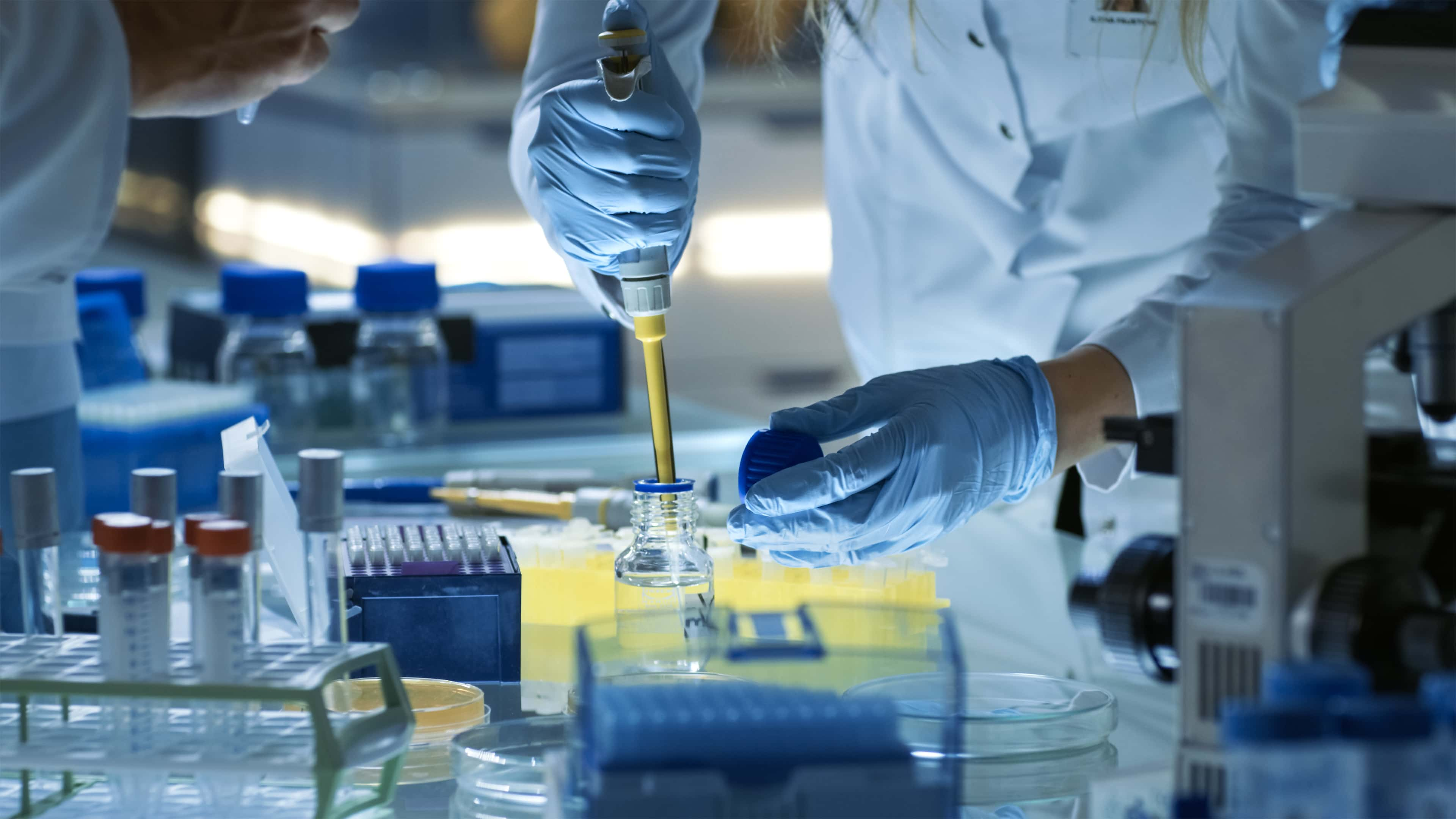A lab tech's hand holds a pipette over a bottle in a lab